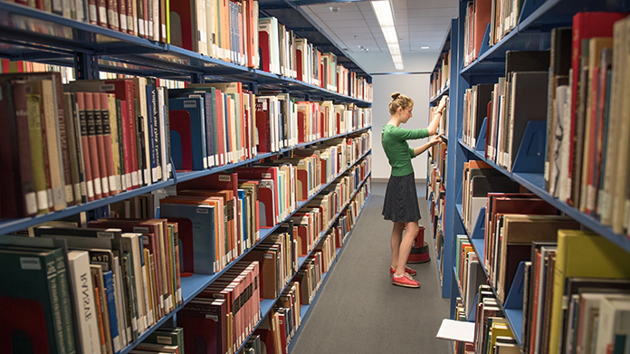 Student browsing the stacks of books in the art library