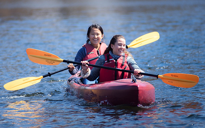 Two students paddling a canoe on the pond
